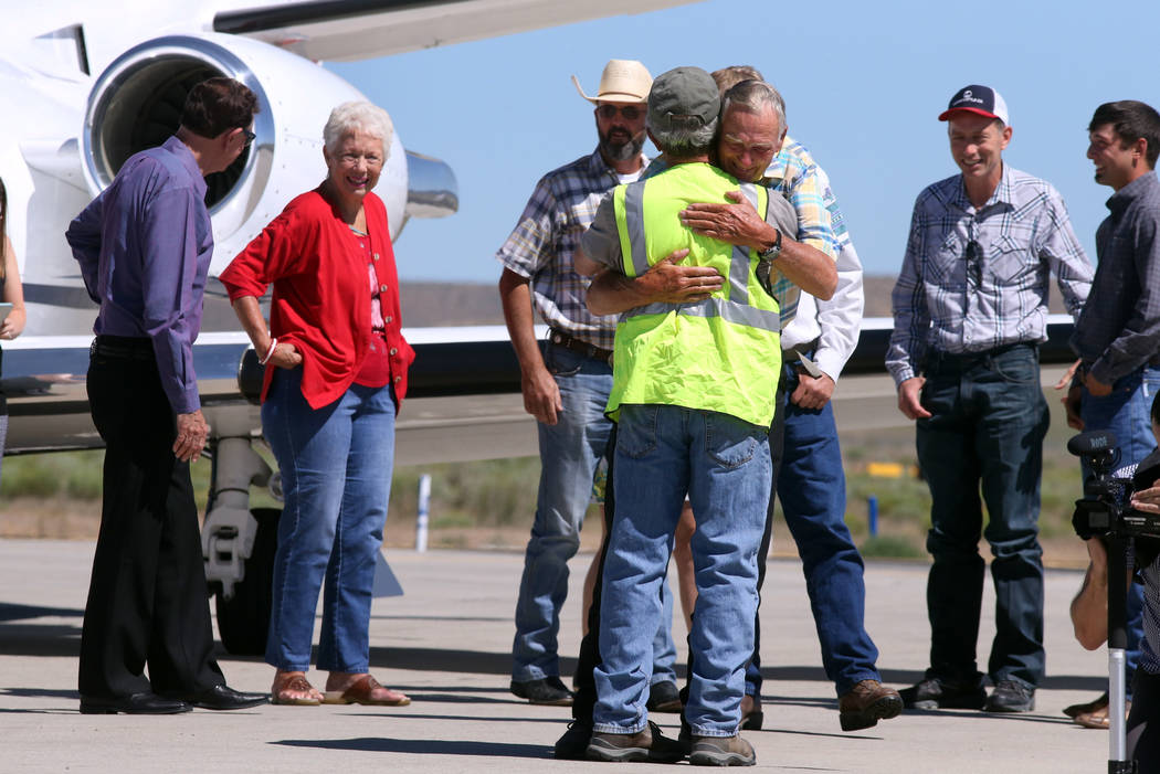 Rancher Dwight Hammond Jr., center, is embraced after arriving by private jet at the Burns Municipal Airport, Wednesday, July 11, 2018, in Burns, Ore. Hammond and his son Steven, convicted of inte ...