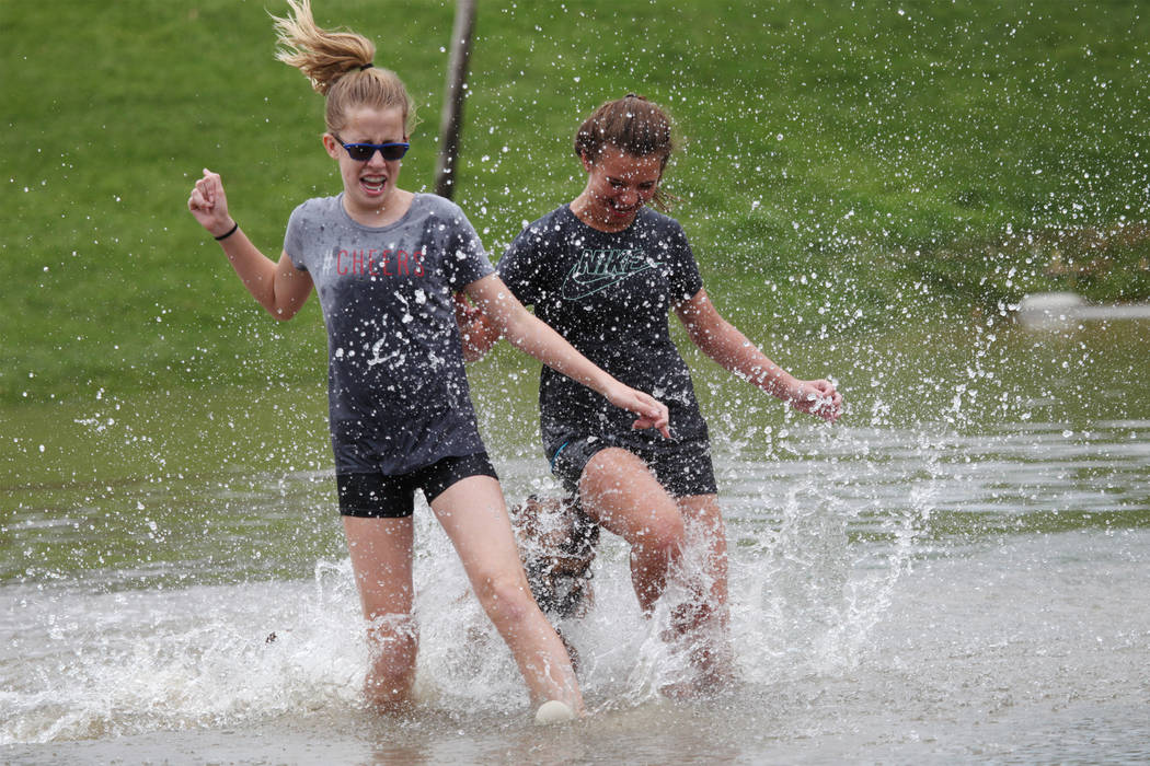Terrylin Lemon, 12, left, and Makenzie Crider, 12, play in the water after a rain storm flooded the park off Wagonwheel Drive and Old Vegas Trail near U.S. Highway 95 in Henderson, Thursday, July ...