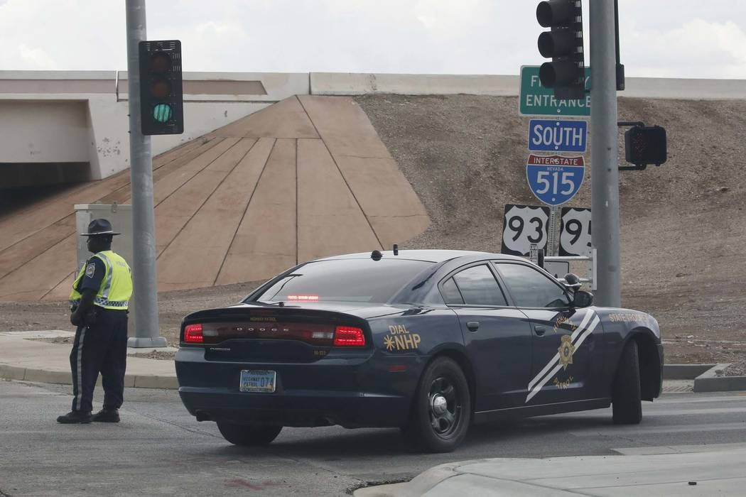 A Nevada Highway Patrol officer blocks entrance to a southbound Interstate 515 on ramp (U.S. Highway 95) in Henderson, Thursday, July 12, 2018. Thunderstorms have caused flash floods in the Hender ...