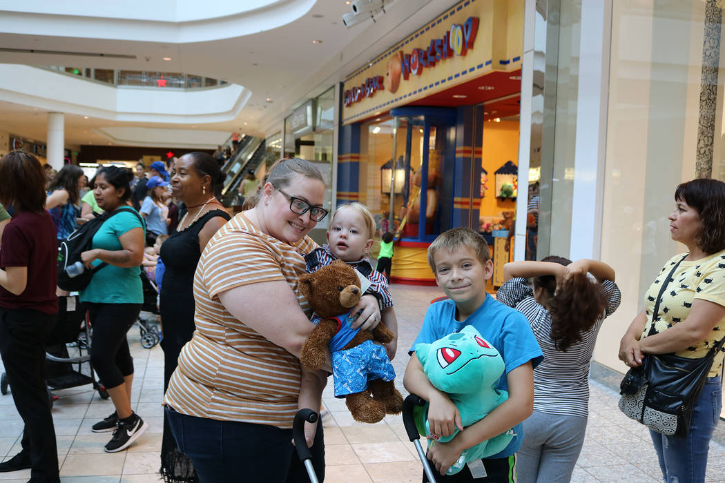 "Jessica, Blake (age 1) and Skylar (age 9) stood in line for four hours before entering the Build-A-Bear store during Build-A-Bear's ""Pay Your Age"" promotion at Galleria Mall in Henderson on July 1 ..."