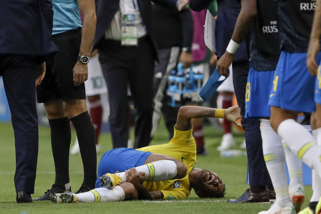 Brazil's Neymar lies on the ground during the round of 16 match between Brazil and Mexico at the 2018 soccer World Cup in the Samara Arena, in Samara, Russia, Monday, July 2, 2018. (AP Photo/Andre ...