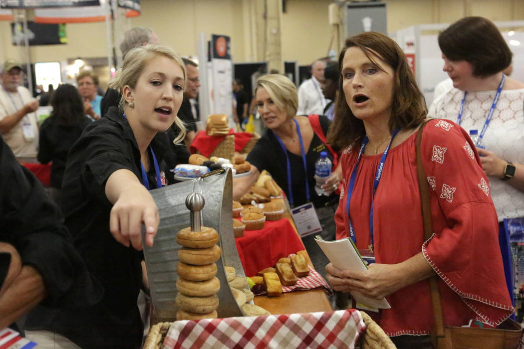 Christine Collins of the Bake Crafters Food Company, points out products to Lory Hayon, registered dietitian for the Clark County School District, during the annual conference of the School Nutrit ...