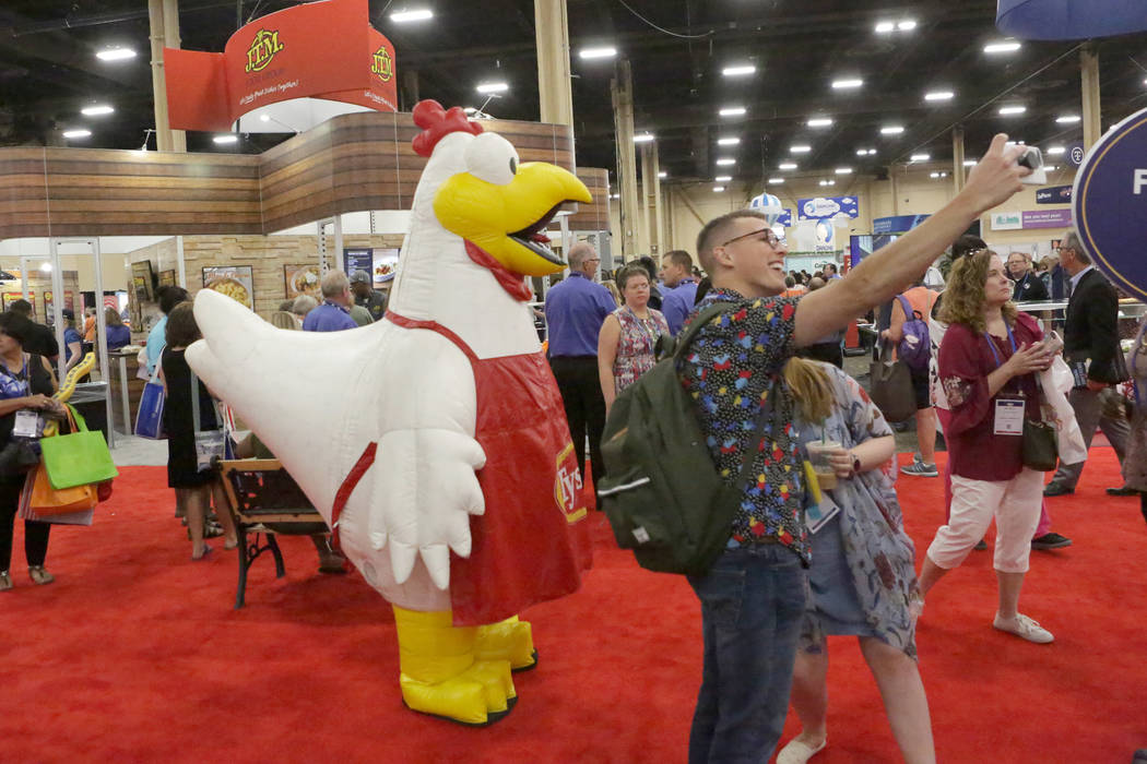 Brandon Rabbitt, director of school nutrition for the Watertown School District in Massachusetts grabs a quick selfie with the Tyson chicken during the annual conference of the School Nutrition As ...