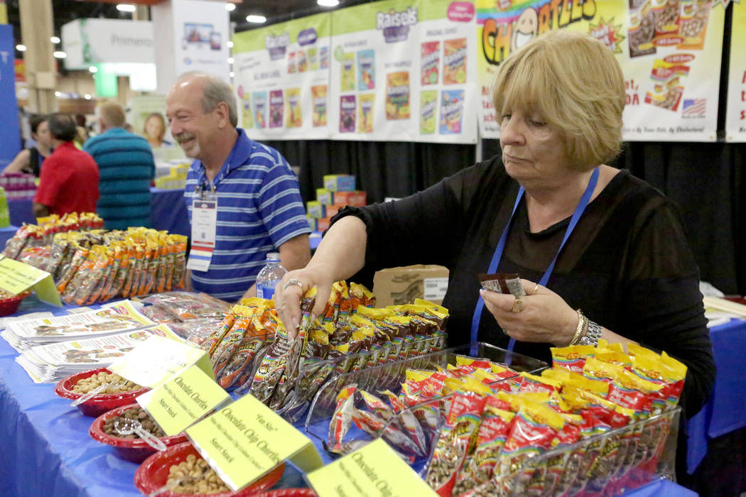 Pat Bana, right, restocks product at the Raisels-Chortles booth during the annual conference of the School Nutrition Association at Mandalay Convention Center on Tuesday, July 10, 2018. Michael Qu ...