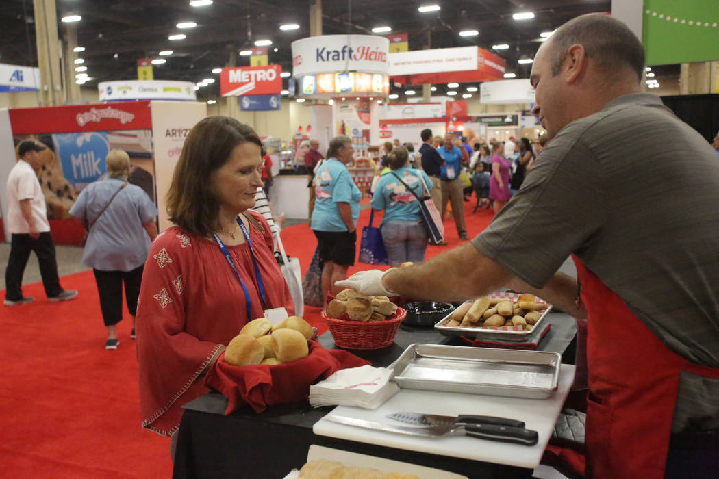 Mike Bridgford, regional manager of Bridgford Foods offers samples to Clark County School District dietitian Lory Hayon at the annual conference of the School Nutrition Association at Mandalay Con ...