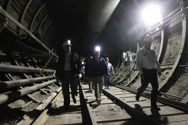 U.S. Rep. John Shimkus, R-Ill., Rep. Bob Latta, R-Ohio and Rep. Cresent Hardy, R-Nev., walk along the train tracks during a congressional tour of the Yucca Mountain exploratory tunnel Thursday, Ap ...