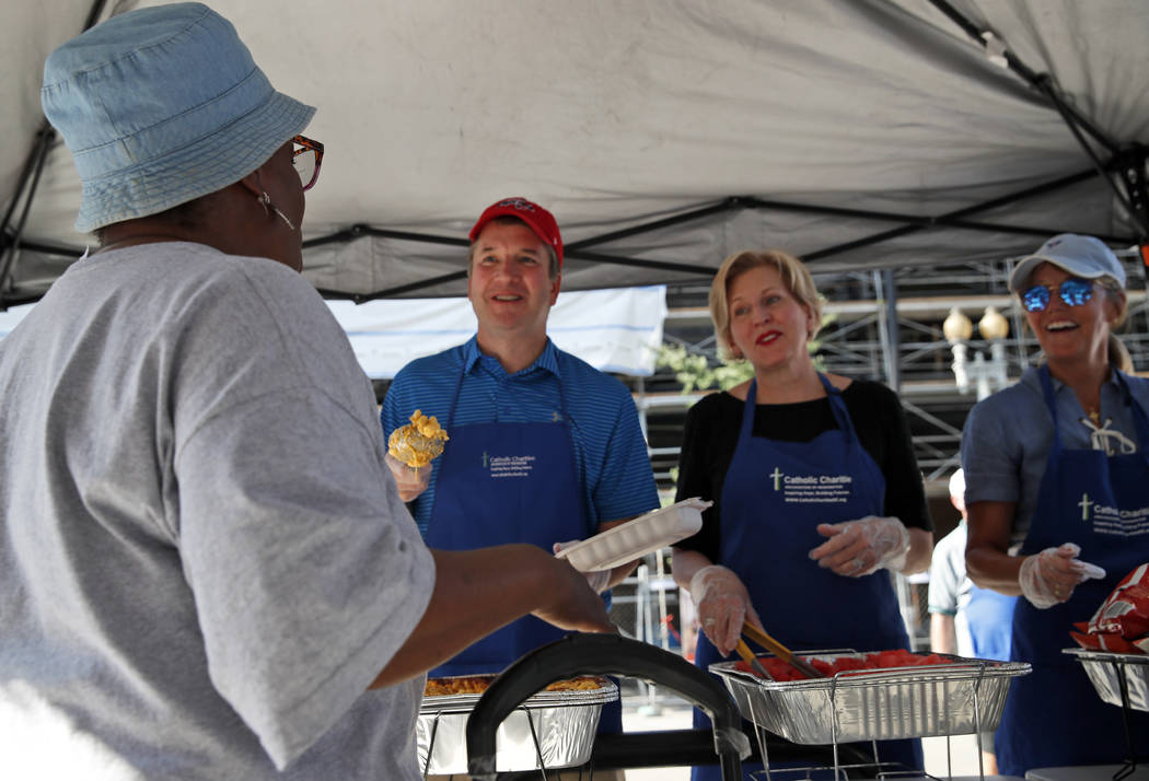 Supreme Court nominee Brett Kavanaugh, second from left, serves macaroni and cheese to the homeless as he volunteers with Catholic Charities, Wednesday, July 11, 2018 in Washington. (AP Photo/Alex ...