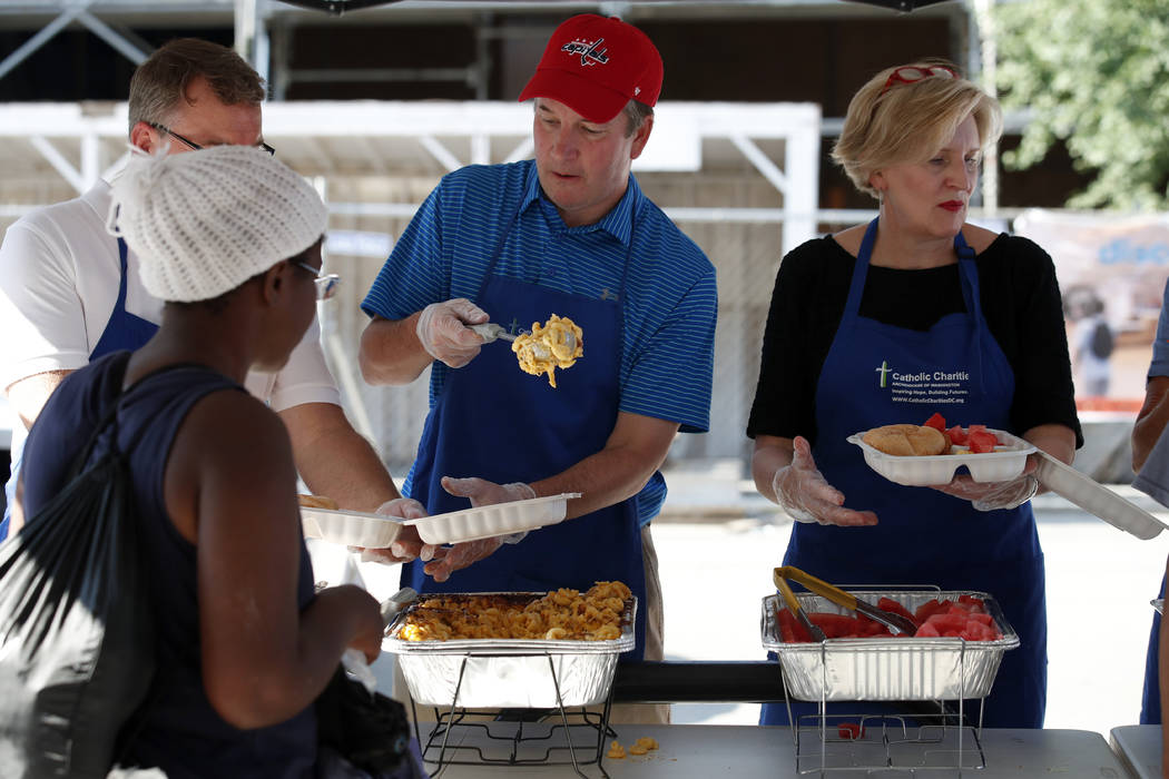 Supreme Court nominee Brett Kavanaugh, center, serves macaroni and cheese to the homeless as he volunteers with Catholic Charities, Wednesday, July 11, 2018 in Washington. (AP Photo/Alex Brandon)