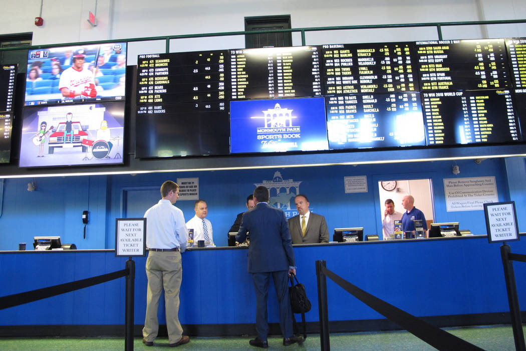 This June 14, 2018 photo shows staff at Monmouth Park racetrack in Oceanport N.J. preparing to begin taking sports bets moments before it became legal in New Jersey. State gambling regulators on T ...
