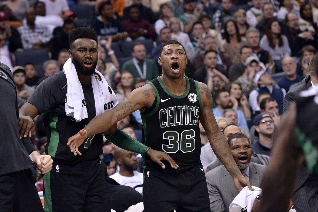 Boston Celtics guard Jaylen Brown (7), and guard Marcus Smart (36) react after guard Terry Rozier scored in the second half of an NBA basketball game against the Memphis Grizzlies, Saturday, Dec. ...