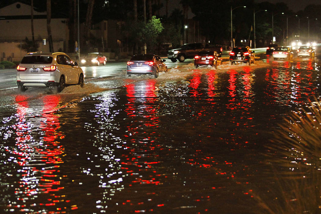 Cars go through a flooded street at the intersection of Sahara and Decatur in Las Vegas on Saturday, July 14, 2018. (Chitose Suzuki/Las Vegas Review-Journal)