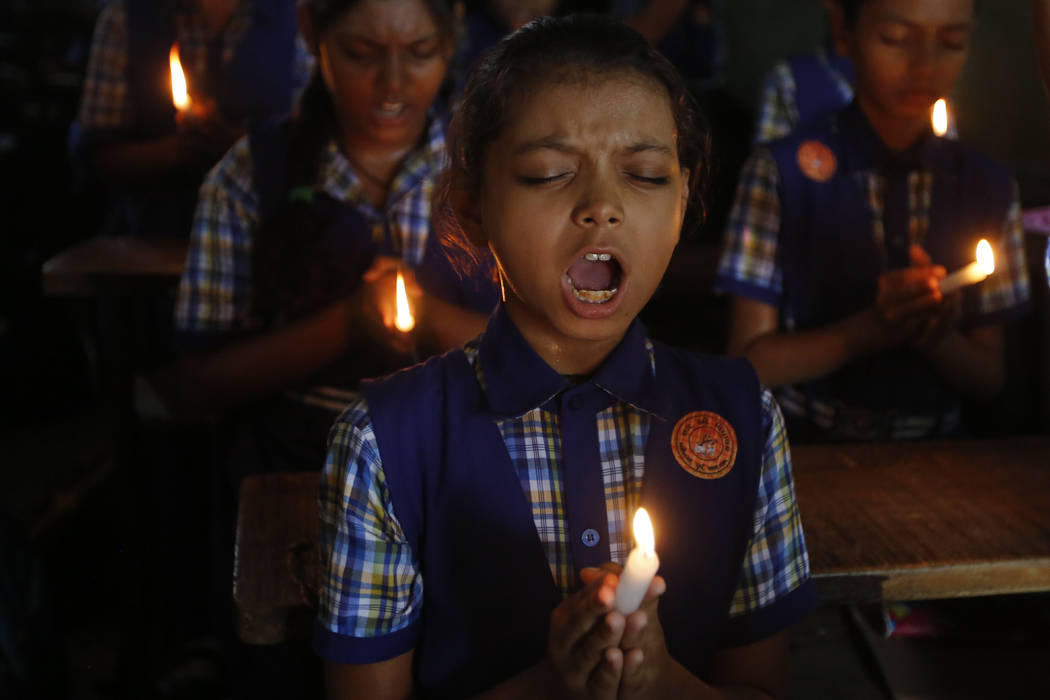 Indian students hold candles and pray for boys and their soccer coach who have been trapped since June 23, in Mae Sai, Chiang Rai province, northern Thailand, at a school in Ahmadabad, India, Mond ...