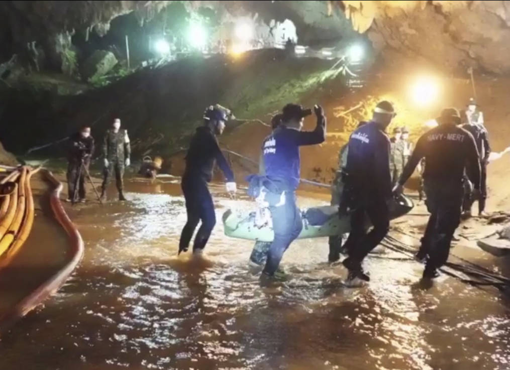This undated from video released via the Thai NavySEAL Facebook Page on Wednesday, July 11, 2018, shows rescuers hold an evacuated boy inside the Tham Luang Nang Non cave in Mae Sai, Chiang Rai pr ...