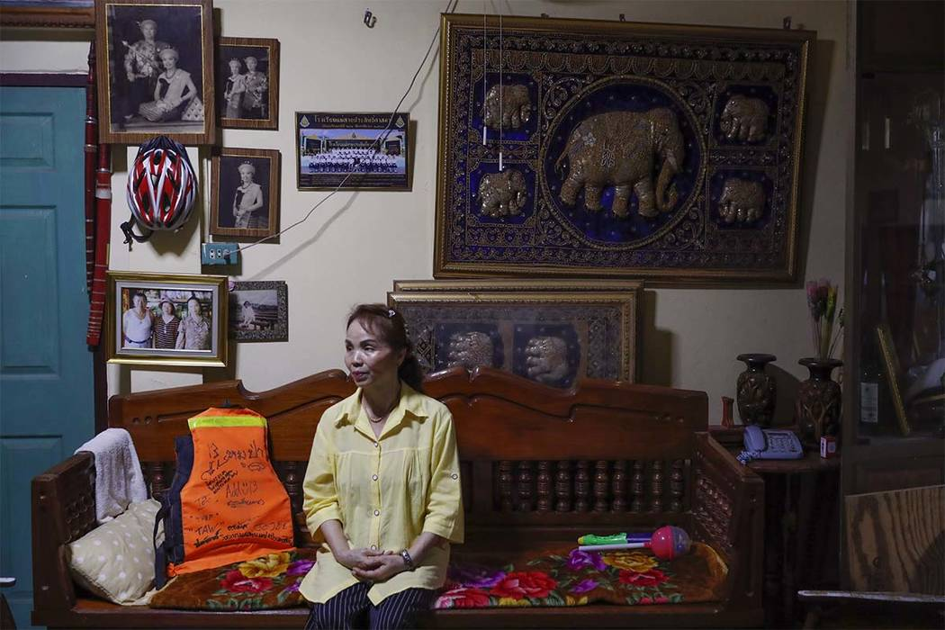 Kameay Promthep, grandmother of Duangpetch Promthep, one of the rescued Thai boys, sits next to her grandson's life vest as she speaks during an interview at their home in Mae Sai district, Chiang ...