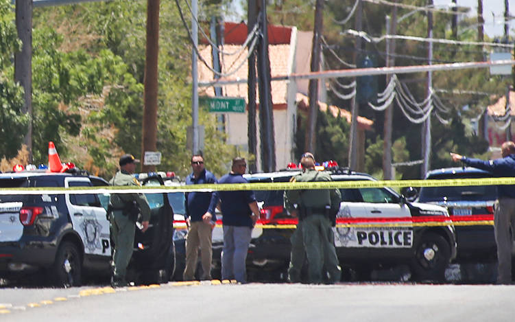 Members of the Metropolitan Police Department near Bruce and Ogden streets after an officer-involved shooting in Las Vegas, Wednesday, July 11, 2018. The school nearby, Hollingsworth Elementary, r ...