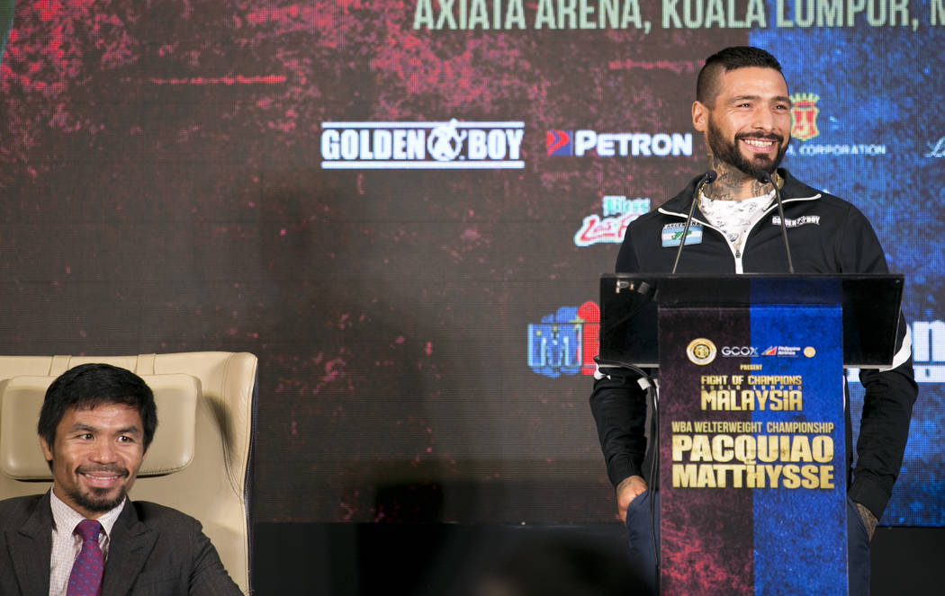 Argentine WBA welterweight champion Lucas Matthysse speaks as Philippine senator and boxing hero Manny Pacquiao smiles during a press conference in Kuala Lumpur, Malaysia, Thursday, July 12, 2018. ...
