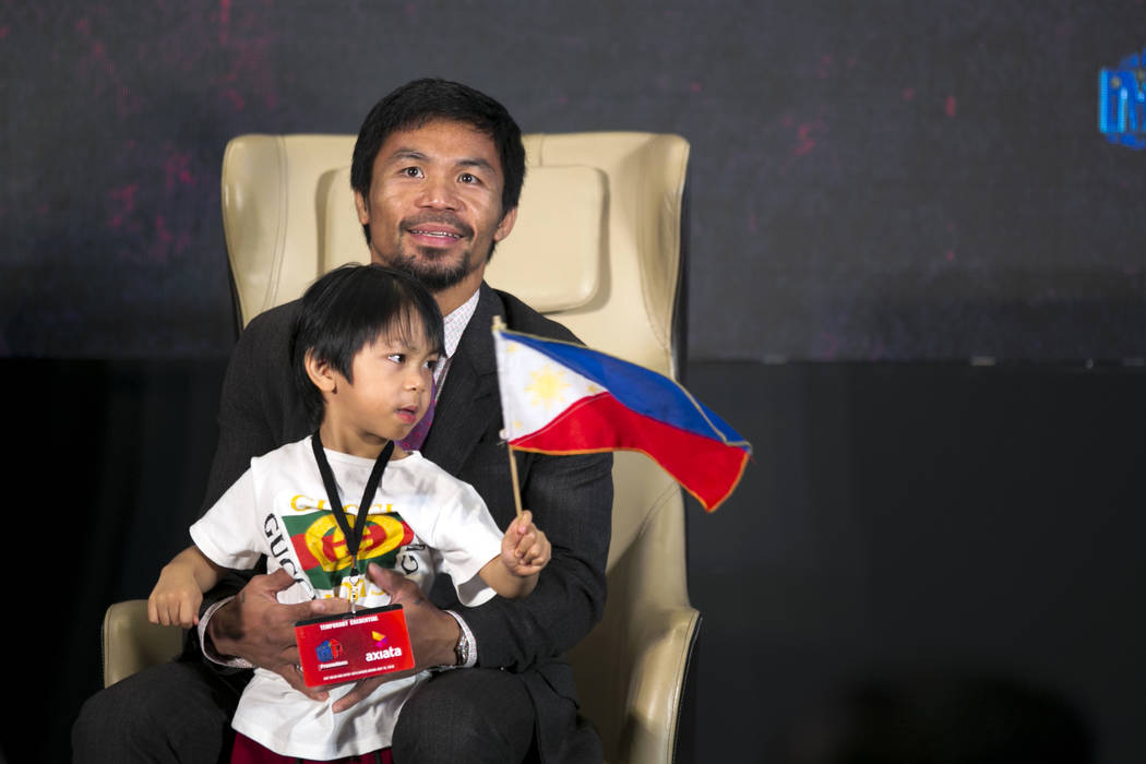 Philippine senator and boxing hero Manny Pacquiao poses with his son, Israel Paquiao, during a press conference in Kuala Lumpur, Malaysia, Thursday, July 12, 2018. Pacquiao and Argentine WBA welte ...