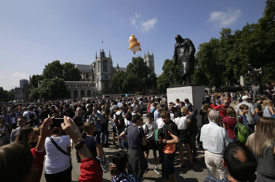 People take photos as a six-meter high cartoon baby blimp of U.S. President Donald Trump hovers next to the statue of former British Prime Minister Winston Churchill, as it is flown as a protest a ...