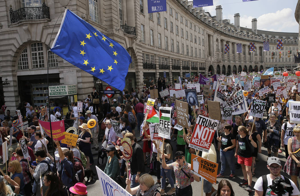 "Protestors hold banners and an EU flag during the ""Stop Trump"" Women's March in London, Friday, July 13, 2018. President Donald Trump's pomp-filled welcome to Britain was overshadowed Friday by an ..."