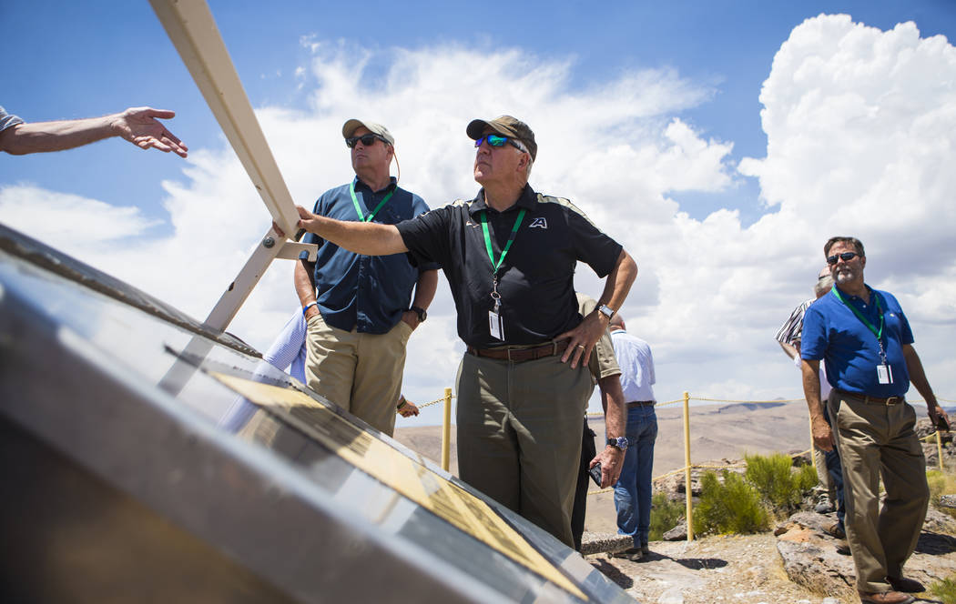 U.S. Rep. John Shimkus, R-Ill., center, listens to Wiilliam Boyle of the Department of Energy's Office of Nuclear Energy, not pictured, at the crest of Yucca Mountain during a congressional tour n ...