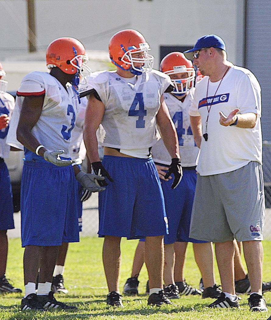 Coach of Bishop Gorman football team David White right talks with line backer Ryan Reynolds 4 & running back Demarco Murray 3, Thursday Aug. 19, 2004. View photo by Henry Vargas. Henry Vargas
