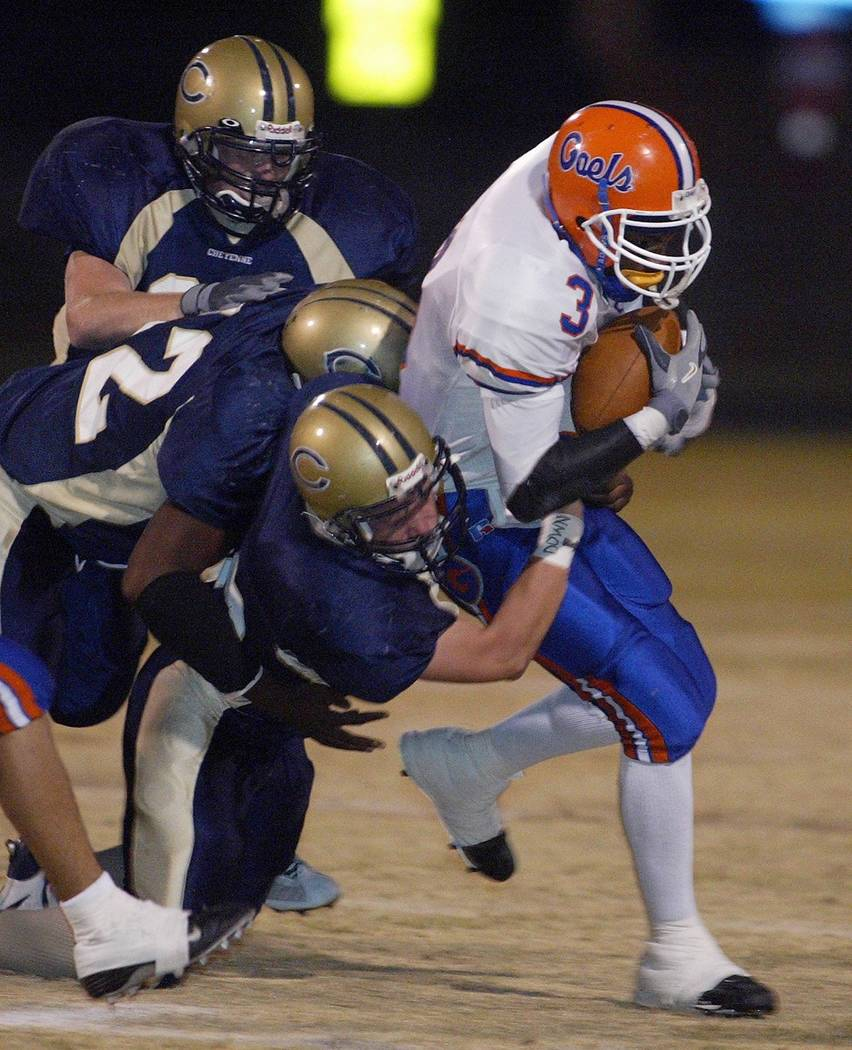 DeMarco Murray of Bishop Gorman High School gets tackled in the first half by players from Cheyenne High School Friday, Sept. 19, 2003 at Cheyenne High School. photo by John Locher