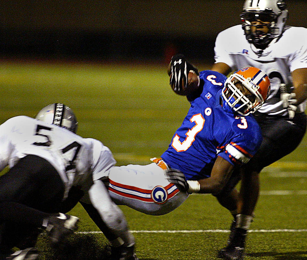 Bishop Gorman's DeMarco Murray is tackled in the 2nd quarter by Palo Verde's Trevor Worpell, left and Sam Ewalefo. RJ photo by Ralph Fountain.