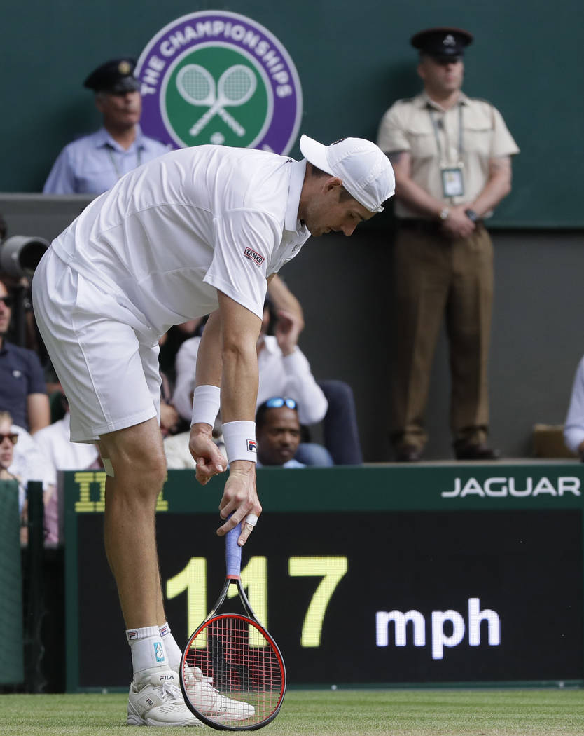 John Isner of the United States pauses after stumbling as he returned the ball to South Africa's Kevin Anderson during their men's singles semifinals match at the Wimbledon Tennis Championships, i ...