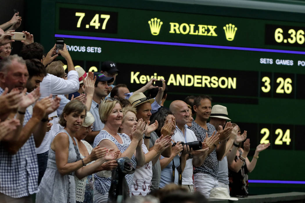 Spectators applaud as the scoreboard displays the final score in the men's singles semifinals match in which John Isner of the United States was defeated by South Africa's Kevin Anderson, at the W ...
