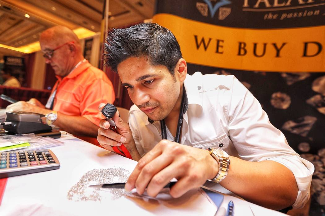 Ankur Savani, president of LosAngeles-based Palak Diam, examines diamonds during the annual Pawn Expo at The Mirage in Las Vegas on Thursday, July 12, 2018.