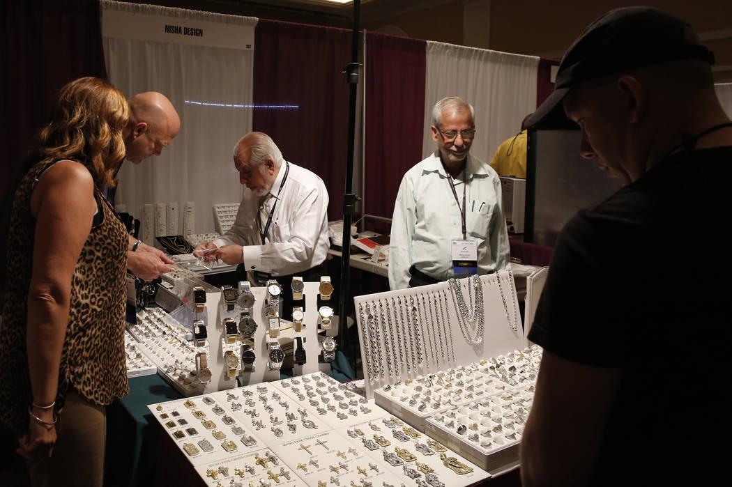 George Chandiramani, center, and J.C. Ramesh, second right, of Nisha Design help customers at Pawn Expo at the Mirage hotel-casino on Thursday, July 12, 2018, in Las Vegas. Bizuayehu Tesfaye/Las V ...