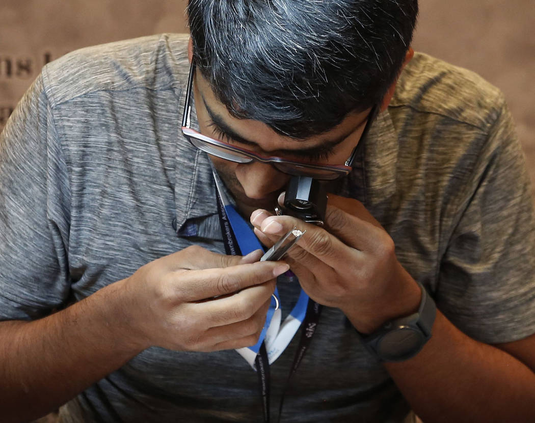 Bhavesh Shah of Aagam Creation checks the quality of a diamond's cut at Pawn Expo at the Mirage hotel-casino on Thursday, July 12, 2018, in Las Vegas. Bizuayehu Tesfaye/Las Vegas Review-Journal @b ...