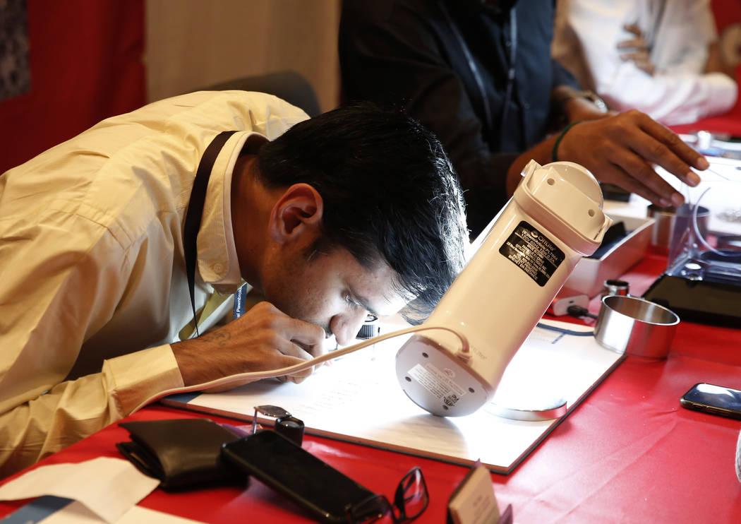 Anil Dhameliya of Star Buyers checks the quality of a diamond's cut at Pawn Expo at the Mirage hotel-casino on Thursday, July 12, 2018, in Las Vegas. Bizuayehu Tesfaye/Las Vegas Review-Journal @bi ...