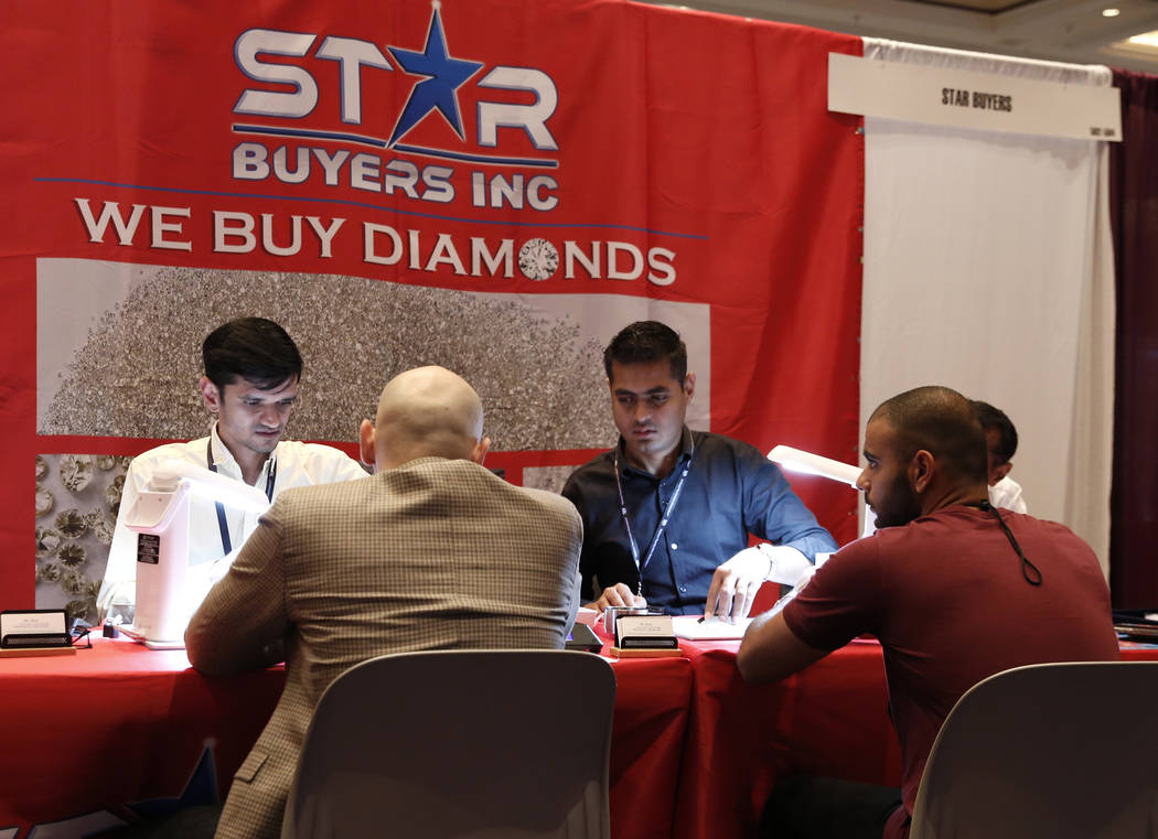Anil Dhameliya, left, and Nick Godhani, second right, of Star Buyers talk to diamond sellers at Pawn Expo at the Mirage hotel-casino on Thursday, July 12, 2018, in Las Vegas. Bizuayehu Tesfaye/Las ...