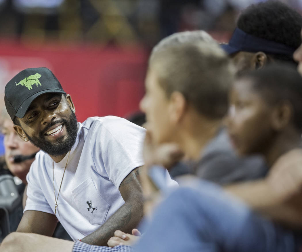 Celtics star point guard Kyrie Irving, left, shares a laugh with friends during Boston's NBA Summer League game with the New York Knicks on Thursday, July 12, 2018, at the Thomas & Mack Center ...