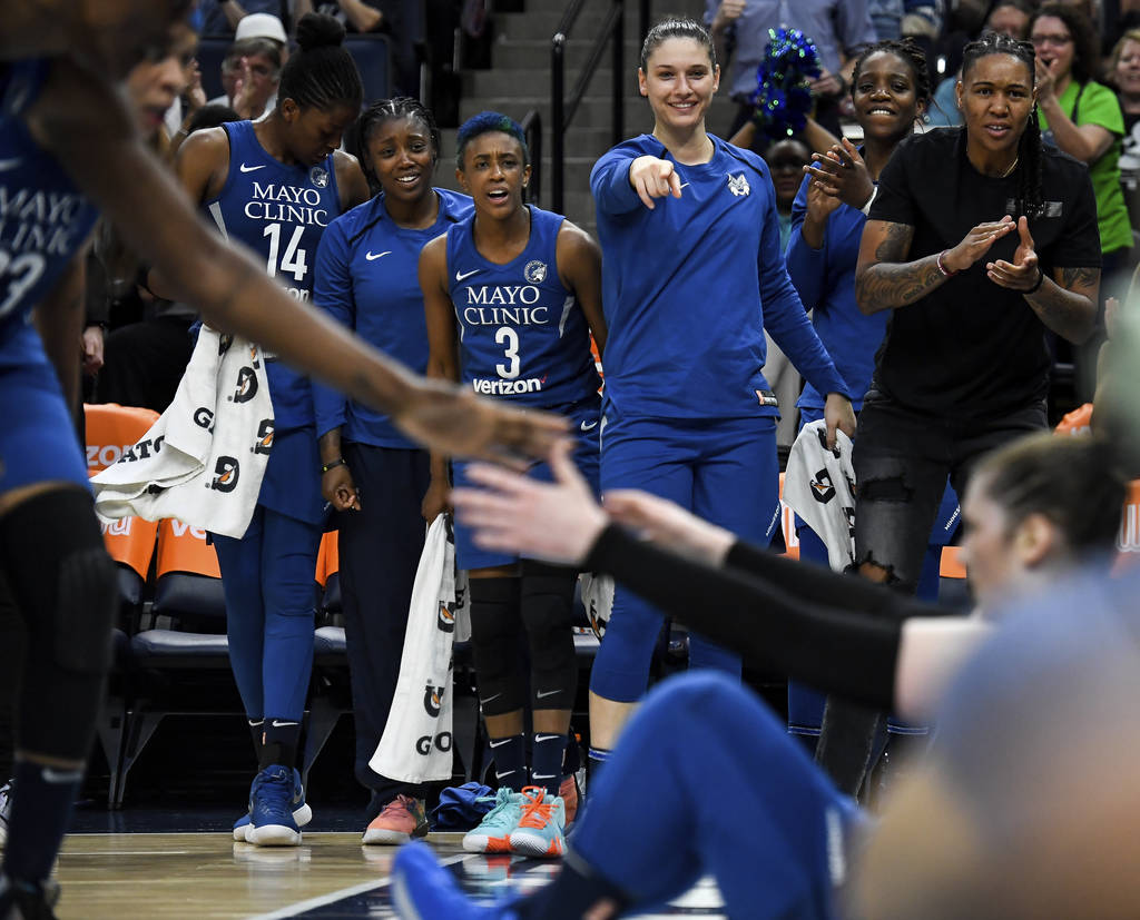 The Minnesota Lynx bench celebrates a layup with an and-one opportunity scored by Lynx guard Lindsay Whalen, who gets a hand up from the court during the first half of a WNBA basketball game again ...