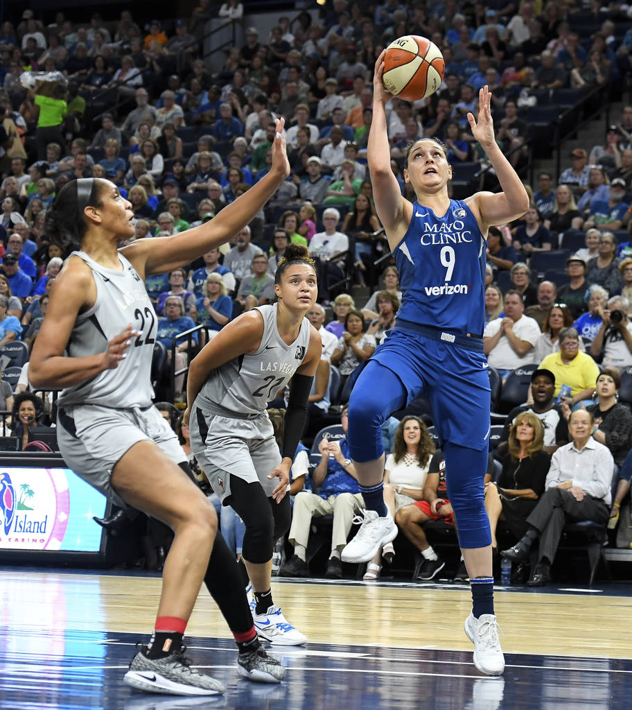 Minnesota Lynx forward Cecilia Zandalasini (9) scores a layup as Las Vegas Aces center A'ja Wilson (22) and guard Kayla McBride (21) defend during the first half of a WNBA basketball game Friday, ...