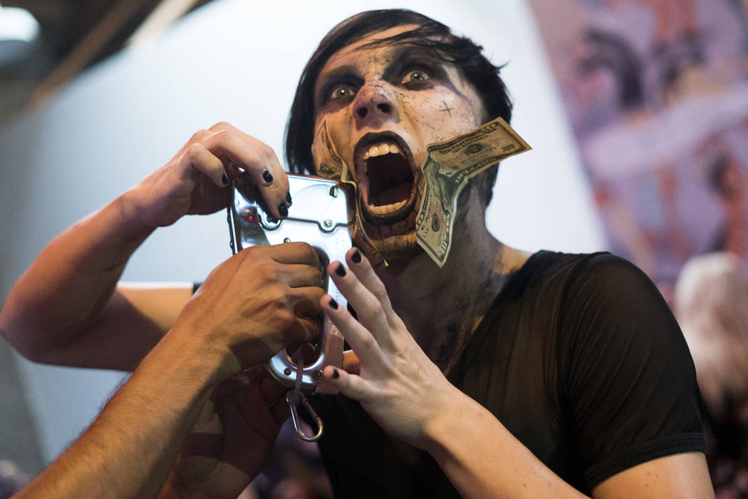 "Austin ""Auzzy Blood"" Punton, 22, sideshow performer, staples dollar bills to his face at The Dark Arts Market at Cornish Pasty Co. in Las Vegas, Friday, July 13, 2018. Hundreds ..."