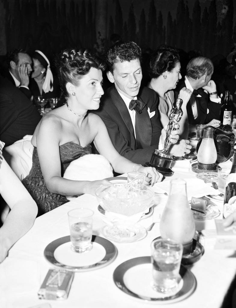 """In this March 11, 1946 file photo, at a crowded table at Ciro's, Frank Sinatra steals a glance at his Oscar which he won for his performance in the film """"The House I Live In,"""" as his wife Nancy lo ..."""