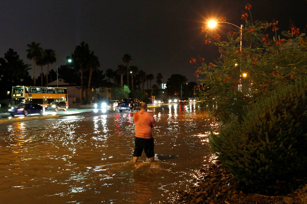 A man walks through a flooded street at the intersection of Sahara and Decatur in Las Vegas on Saturday, July 14, 2018. (Chitose Suzuki/Las Vegas Review-Journal)