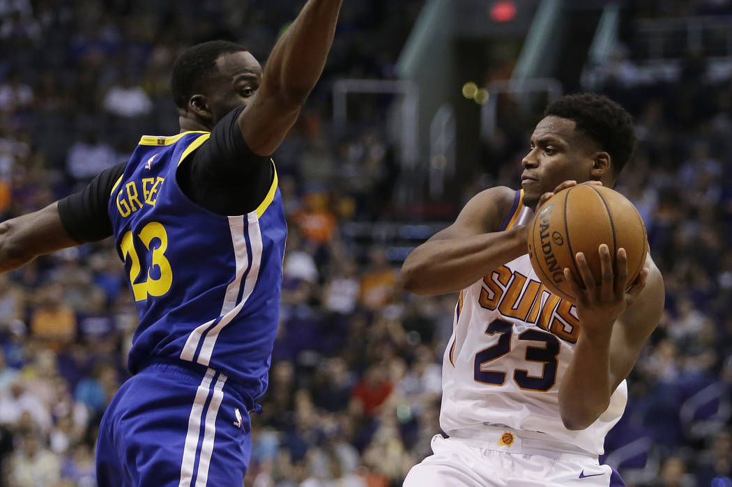 Phoenix Suns forward Danuel House Jr. (23) drives past Golden State Warriors forward Draymond Green in the second half during an NBA basketball game, Sunday, April 8, 2018, in Phoenix. The Warrior ...