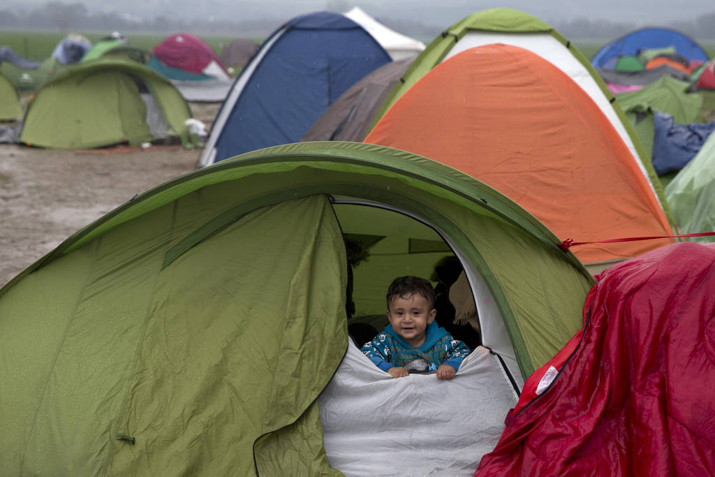 A Syrian children looks out from a tent during rainfall, as refugees wait to be allowed to cross the the Greek-Macedonian border near the northern Greek village of Idomeni in 2016. (AP Photo/Petro ...