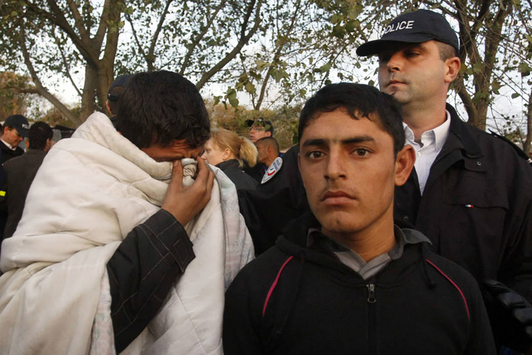 """A police officer, top right, watches migrants in the camp known as the """"Jungle"""" in Calais, northern France, in 2009. (AP Photo/Michel Spingler, file)"""