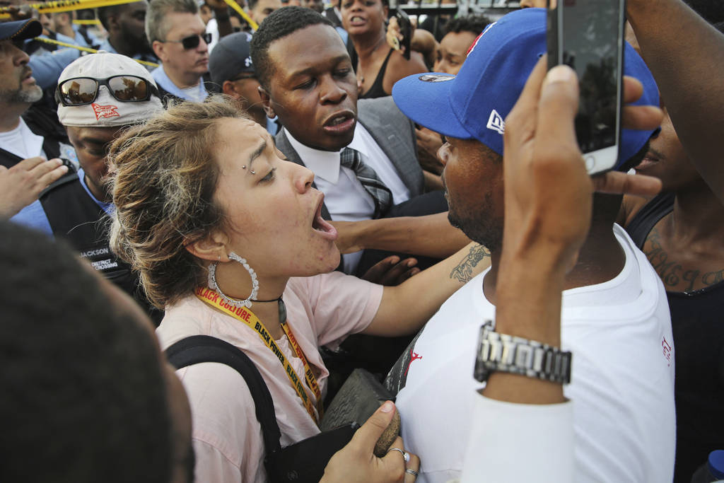 A woman tries to calm a man down as he yells at a police officer at the scene of a police involved shooting in Chicago, on Saturday, July 14, 2018. (Nuccio DiNuzzo/Chicago Tribune via AP)
