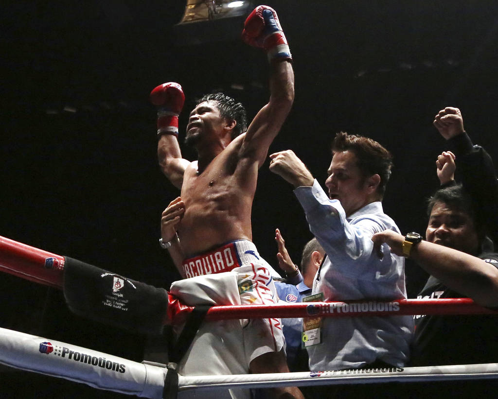 Philippine boxer Manny Pacquiao, center, celebrates after defeating Argentina Lucas Matthysse during their WBA World welterweight title bout in Kuala Lumpur, Malaysia, Sunday, July 15, 2018. Pacq ...