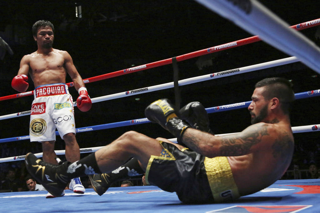 Lucas Matthysse, left, of Argentina falls after receiving a punch by Manny Pacquiao of the Philippines during their WBA World welterweight title bout in Kuala Lumpur, Malaysia, Sunday, July 15, 20 ...