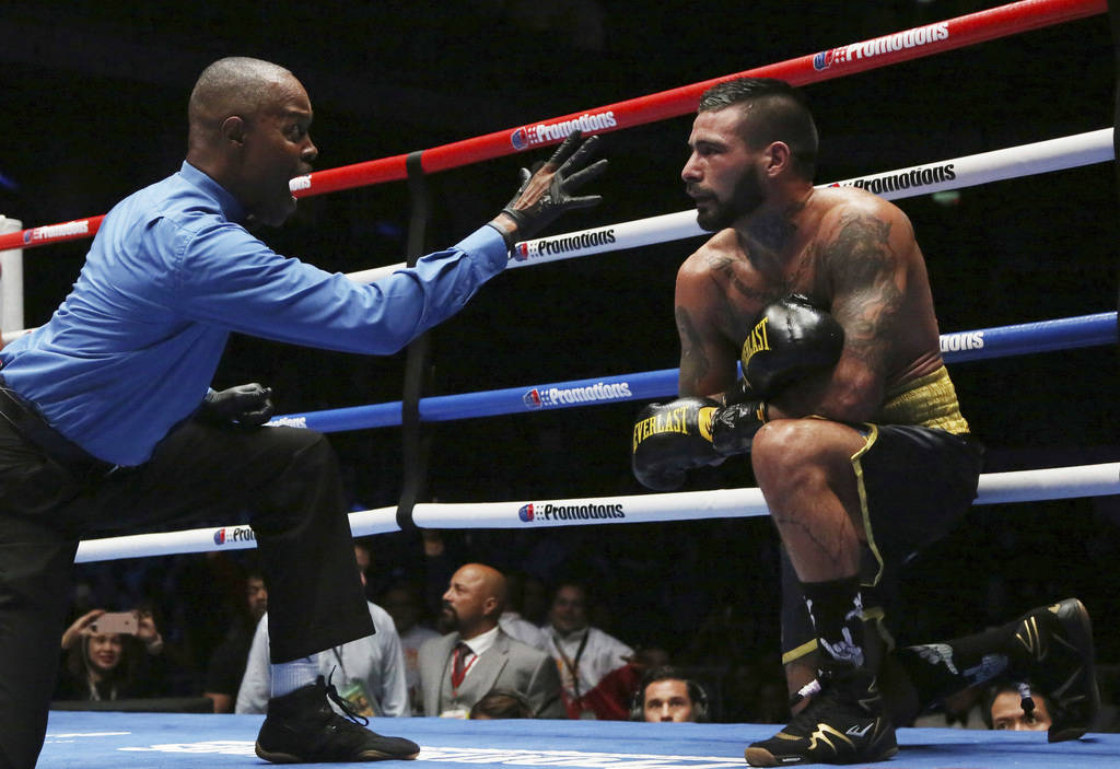 The referee checks Lucas Matthysse of Argentina after falling from a punch from Manny Pacquiao of the Philippines during their WBA World welterweight title bout in Kuala Lumpur, Malaysia, Sunday, ...
