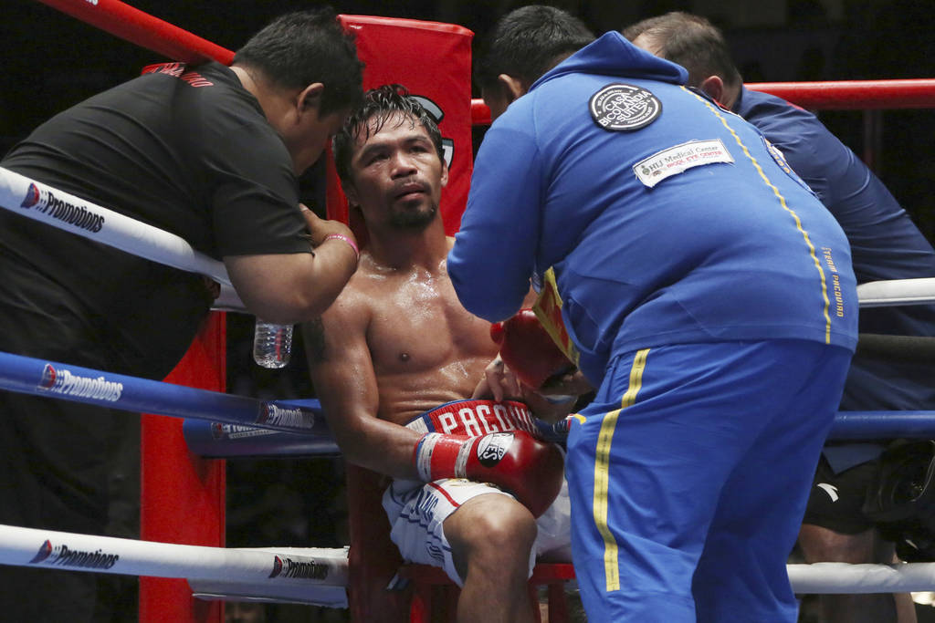 Manny Pacquiao, center, of the Philippines listens to his trainer during WBA World welterweight title bout against Lucas Matthysse of Argentina in Kuala Lumpur, Malaysia, Sunday, July 15, 2018. P ...