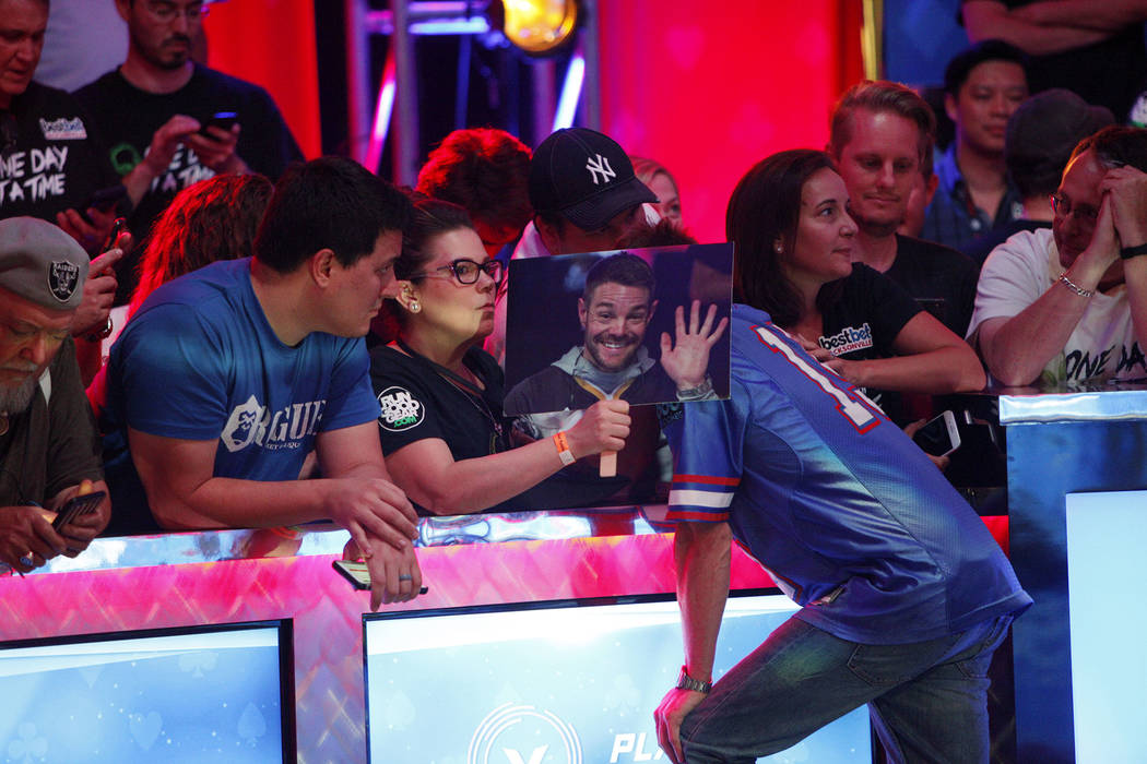 Tony Miles leans in for advice from supporters on day three of the main event final table at the World Series of Poker tournament at the Rio Convention Center in Las Vegas, Saturday, July 14, 2018 ...