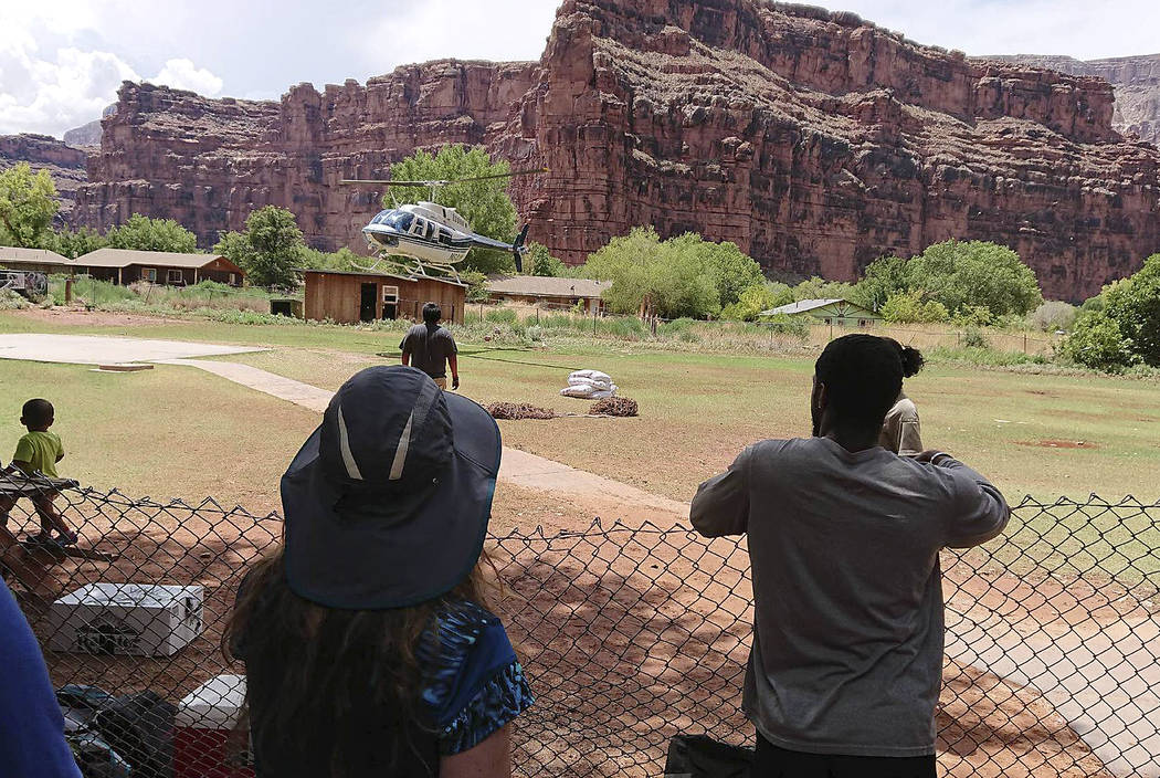 This Thursday, July 12, 2018 photo released by Benji Xie shows a helicopter landing to rescue people from flooding on the Havasupai reservation in Supai, Ariz. Rescue workers were evacuating about ...